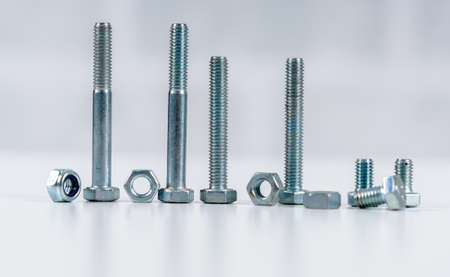 Metal screw, bolt and nuts on white background..