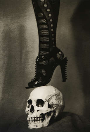 henpecked: The female leg in the shoe is on the human skull. Attention! Real retro technology. The graininess of the photographic film and photo paper is visible. Stock Photo