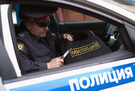 Moscow, Russia, May 19, 2012: A Russian policeman cuts off a police badge from bulletproof vest. Editorial