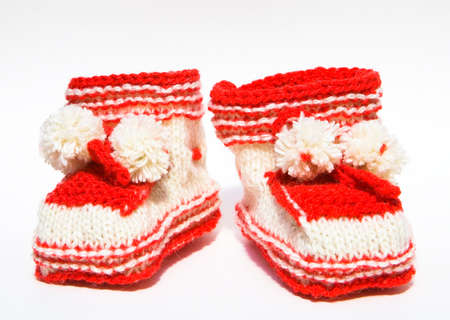 Baby clothes. Red booties with handmade pom-poms. Stock Photo
