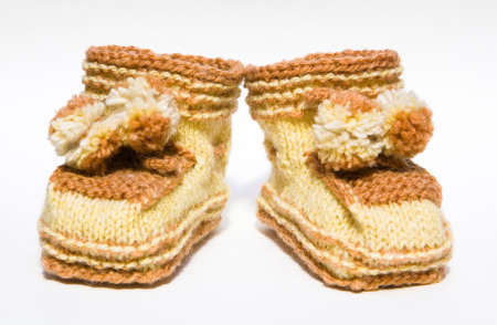 Baby clothes. Brown booties with handmade pom-poms.