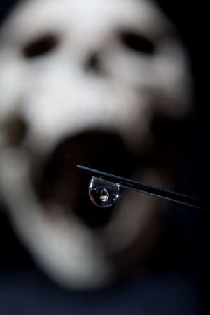 A drop of a drug on the tip of a syringe against the background of a human skull. Still life. Stock Photo