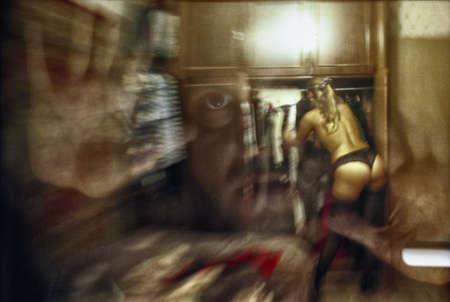 マニアックは、服を着替える美しいほっそりした金髪の少女の背後にある窓からピークします。注意!画像には、写真フィルムの粒状性が含まれています。 写真素材 - 78253335