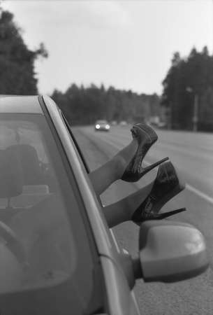 Female feet in high-heeled shoes stick out of the car. Black and white photo. Attention! The image contains the graininess of the photographic film! 版權商用圖片