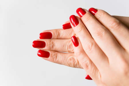 uñas pintadas: Female fingers with a beautiful manicure. Nails are covered with red lacquer. Foto de archivo