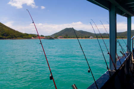 Sea fishing. The fishing rods are leaning against the side of the ship against the background of the hilly coast.