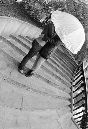 Moscow, Russia, September 16, 2012: Two girls hug under an umbrella on the stairs. Attention! The image contains the graininess of the photographic film!