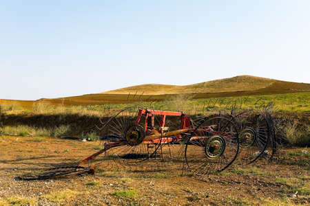 Broken agricultural machinery against the backdrop of fields and hills. Turkey.