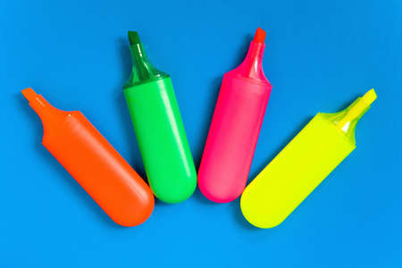 Multicolored markers lie on a blue sheet of paper. Stationery.