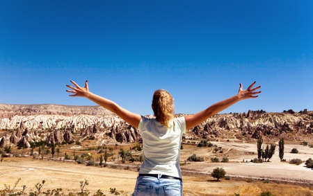 The girl spread her arms out to the sides. Against the background of a mountain landscape.