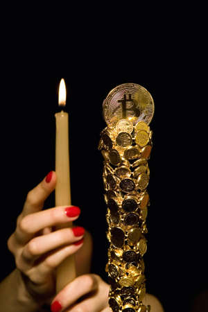 Female hands hold a candle in front of bitcoin. Crypto currency.