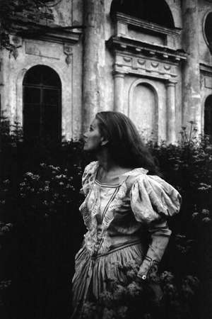 A girl in an antique dress looks away. Attention! The image contains grain and other artifacts of analog photography!