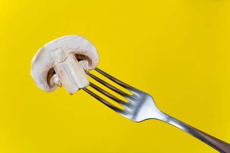 Half a champignon on a fork. On a yellow background.