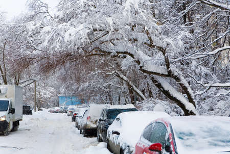 Cars are parked in the yard. Snowfall in Russia.