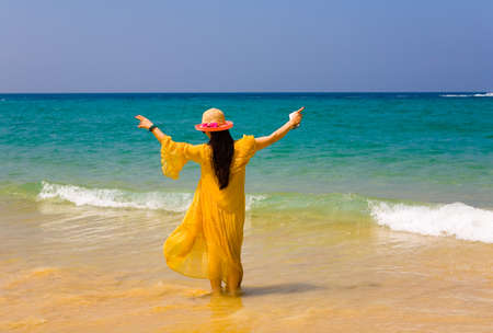 The girl in the yellow dress is standing with her back to the camera. Against the background of the ocean.