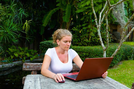 A woman is working on the computer. In the open air.