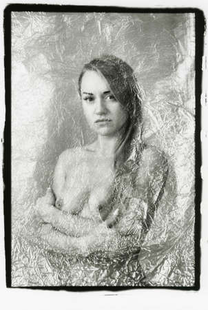 Blonde with a beautiful nude breast. Multiple exposure. Attention! The image contains granularity and other artifacts of analog photography.