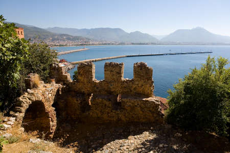 Ruins of an old fortress against the background of the Mediterranean Sea. Alanya.