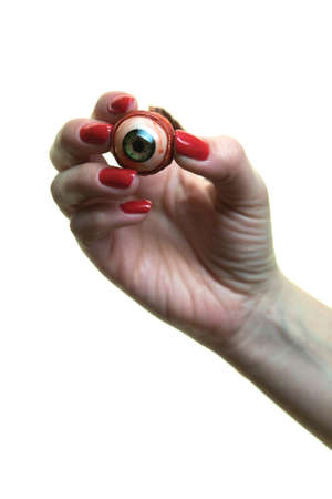 Female fingers with a beautiful red manicure hold a torn eye. Thriller.