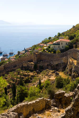 The old fortress wall of Alanya against the background of the sea. Stock Photo