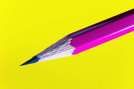 Cheap sharp sharpened pencil on a yellow background. Closeup.