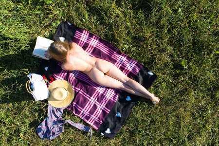 A nudist girl sunbathes in the grass and reads a book. Aerial photography. Standard-Bild