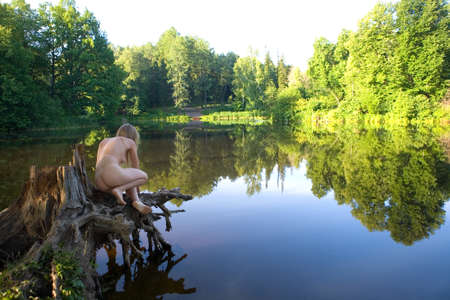 A beautiful naked girl sits on a picturesque stump. Morning in nature.