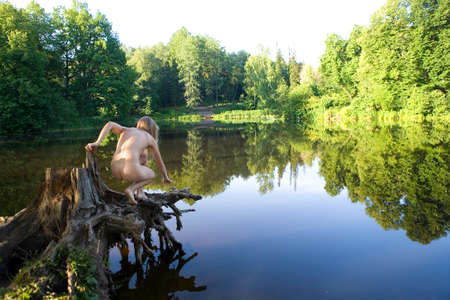 Nude girl on a picturesque stump near the pond. Back view. Imagens