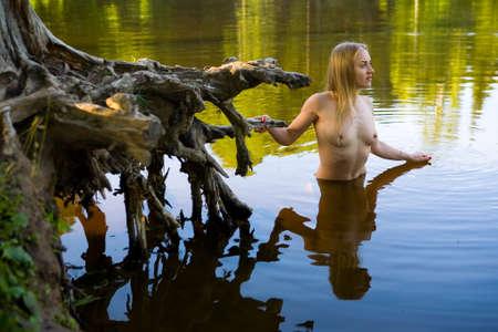 美しい女の子が絵のように美しい切り株の隣の水の中に立っています。自然の中で朝。