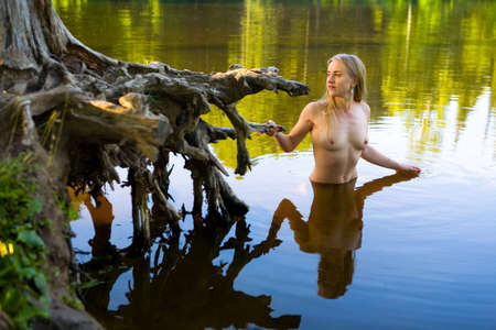 A beautiful girl stands in the water next to a picturesque stump. Morning in nature.