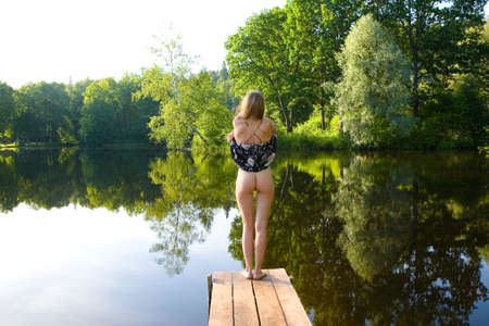 A slender girl undresses on the bridge against the backdrop of a picturesque pond. Erotica and nature.