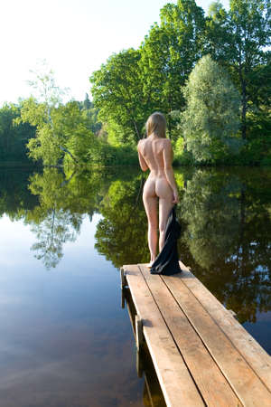 A slender naked girl stands on the bridge against the backdrop of a picturesque pond. Erotica and nature. Banque d'images