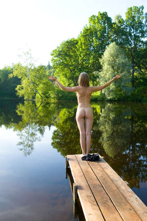 The naked girl stands on the bridge against the backdrop of a picturesque pond. Hands are raised in the sides. Erotica and nature. 免版税图像