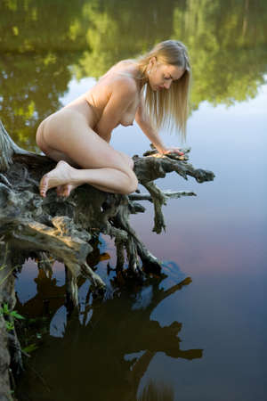 A beautiful naked girl admires her reflection in the water.