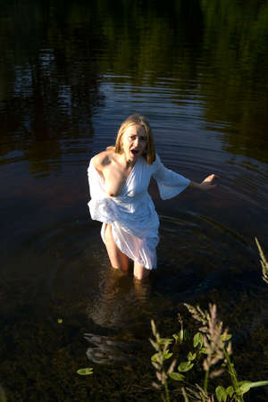 A beautiful girl with a naked breast is standing in the water. Human and nature. 免版税图像 - 106449191