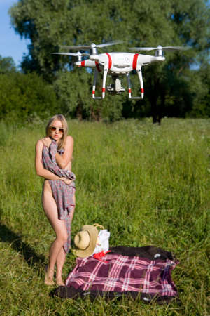 The girl covers her nakedness with her dress. The drone looks at her. Interference in private life. Attention! Focus on the drone! Stock Photo - 106449208