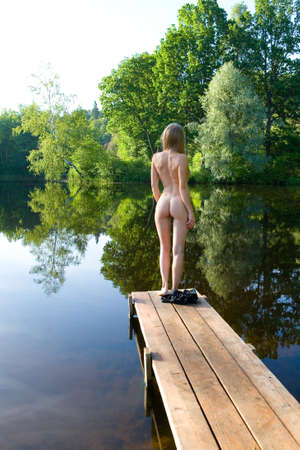 A slender naked girl stands on the bridge against the backdrop of a picturesque pond.
