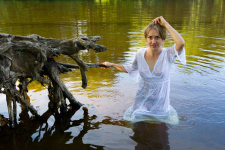 Beautiful girl in a wet translucent white dress in the water. Human and nature.
