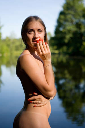 Emotional portrait of a naked girl in an open air. Human and nature. Standard-Bild
