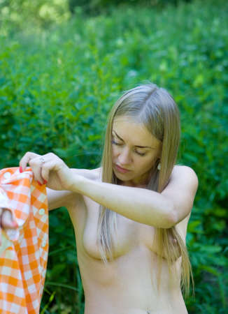 A beautiful blonde with bare chest dresses a dress. Life portrait. Фото со стока