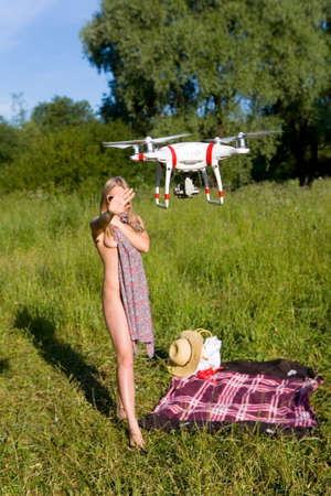 The girl covers her nakedness with her dress. The drone looks at her. Interference in private life. Attention! Focus on the drone!