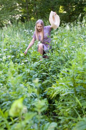 A beautiful blonde makes her way through thickets of tall grass. Human and nature.