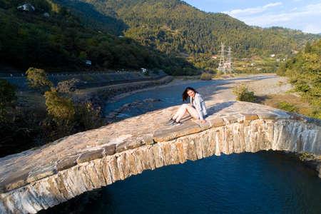 A girl is sitting on an ancient stone bridge. Georgia.
