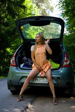 Slanke langbenige blondine naast de auto. De kofferbak is open.