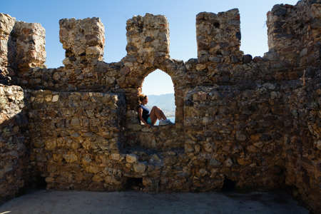 The girl is sitting in the loophole of the fortress wall. Turkey.