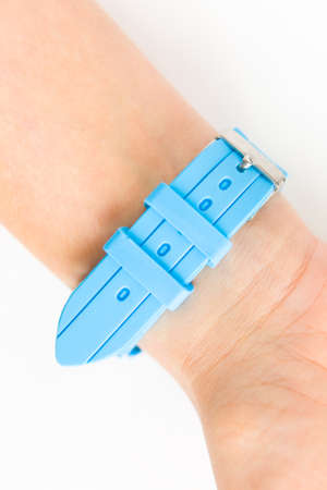 Blue silicone strap on the female wrist. Close-up. 스톡 콘텐츠