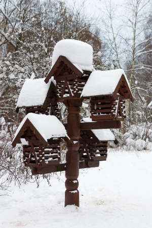 Beautiful wooden feeder for birds and squirrels in the winter forest. Caring for nature.