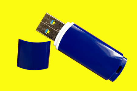 A blue USB stick lies on a yellow background. Isolate closeup. 写真素材