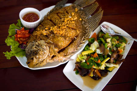 Delicious exotic fried fish with sauce and salad. Thailand food.