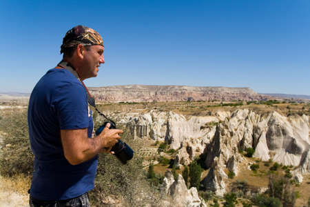 A man with a camera on the background of the mountain landscape of Cappadocia. Travel to Turkey.